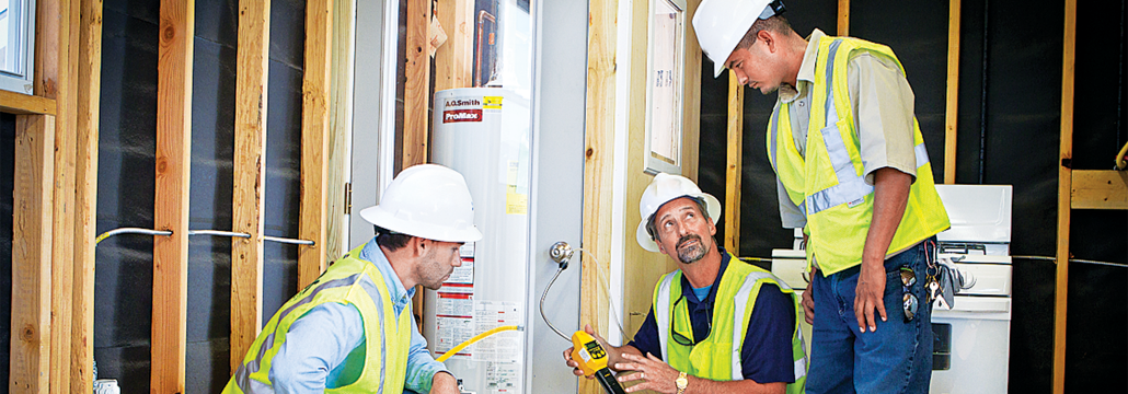 Three utility workers inside a home working on a natural gas water heater