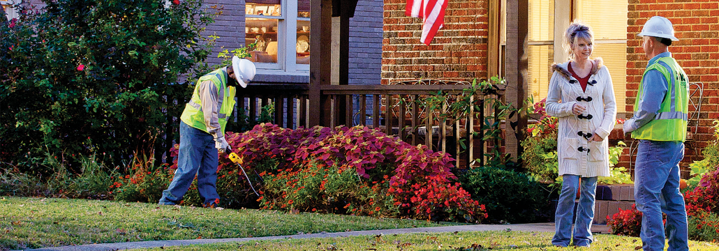 Atmos Energy employee in discussion with a customer on their front lawn.