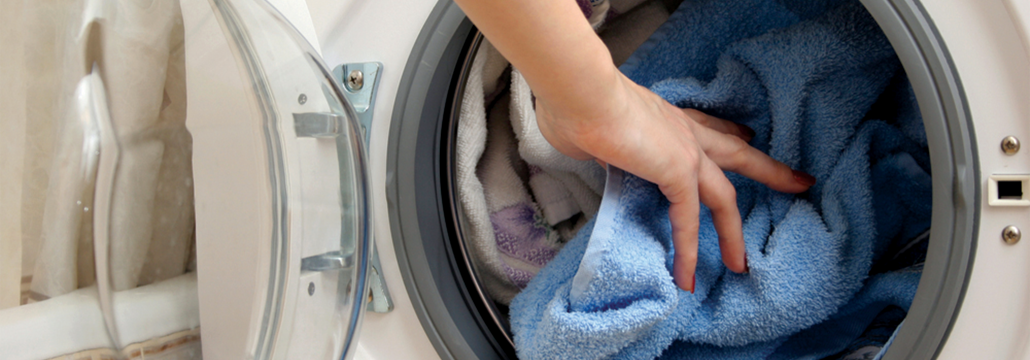 Closeup picture of a woman's hand putting towels in a natural gas dryer.