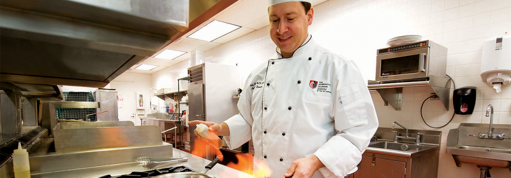 Chef cooking with a pan above a flame on a natural gas stove in a commercial kitchen.