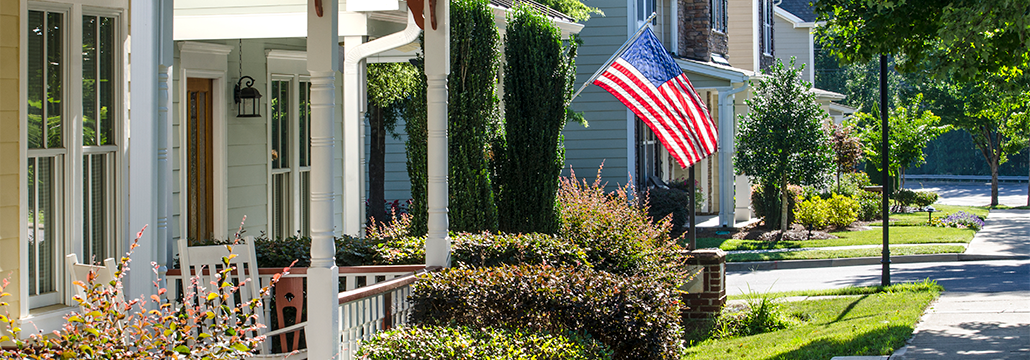 Neighborhood street lined with houses and an American flag.