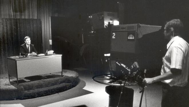 Atmos Energy's founder, Charles K. Vaughan, at a news studio broadcasting on live television, announcing a spinoff of Energas Company by Pioneer Corporation in 1983.