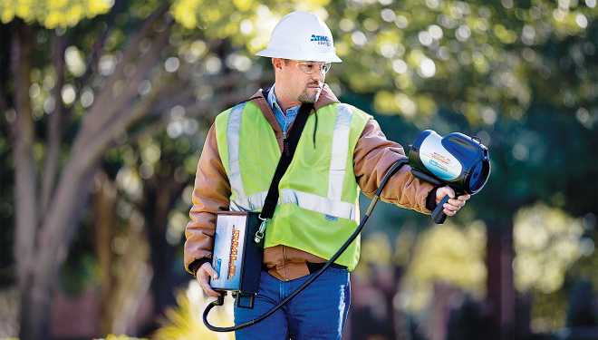 Atmos Energy service tech holding a device in the air that detects natural gas leaks.